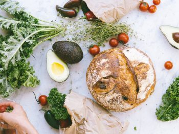 flat lay photograph of bread tomatoes and avocados
